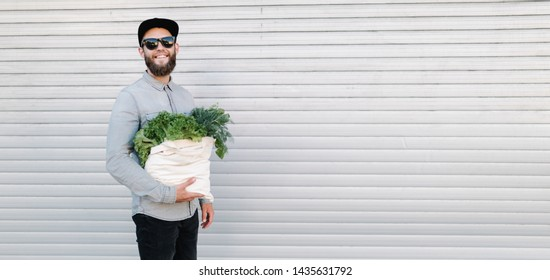 Man holding an eco bag filled with grocery. Vegetables and fruits are hanging from the bag. Ecology concept of environment protection.