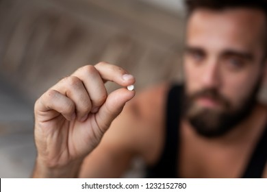 Man holding an ecstasy pill. Focus on the pill