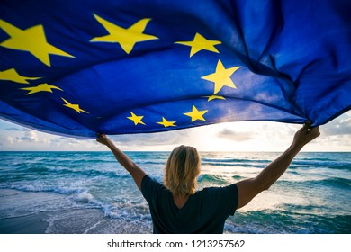Man holding EU European Union flag waving in front of Mediterranean sunrise seascape