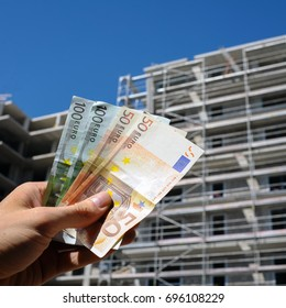 Man holding euro money in front of new building construction process