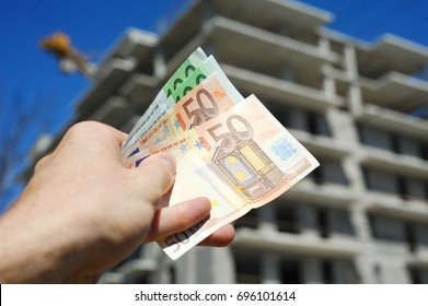 Man holding Euro notes in front of building construction process
