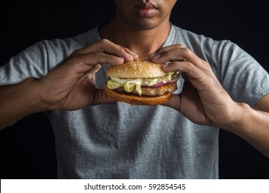 Man holding fast food burger in hands, american meal on a black