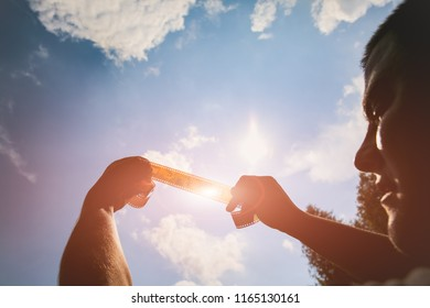 Man is holding film strip in his hands against the sunlight and sky. Guy remembering his childhood memories in the nature. Retro concept on the photo tape.
