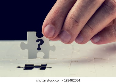 Man holding the final puzzle piece with a question mark hand-drawn on it in his fingers above a jigsaw puzzle conceptual of a problem and the solution.
