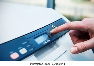 Man holding finger on start button of laser printer