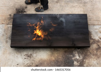 A man holding a fire torch and burning a big piece of oak creating flames and smoke, old japanese shou sugi ban technique