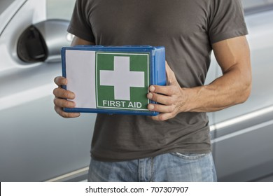 Man holding first aid kit for car.