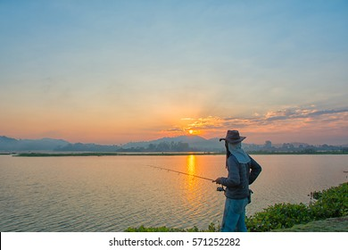 The man was holding a fishing rod in his hand in the morning with a sunrise and fog.Northern District of Chiang Rai, Thailand