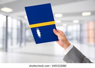 Man Holding Flag of Nauru. Nauru in Hand.