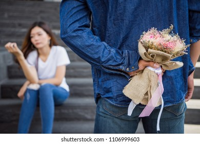 Man holding flower bouquet to give to woman in angry mood. boyfriend hide flower to surprise girlfriend. lovely couple concept.