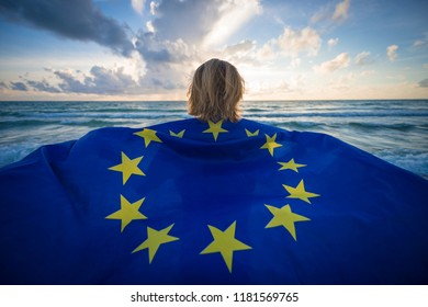 Man holding a fluttering iconic EU flag with circle of stars on beach with stormy turbulent seas in the channel at sunrise