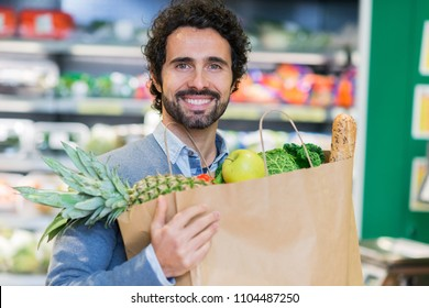 Man holding food bag in a grocery store