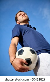 Man holding a football outdoors with the sky on the background