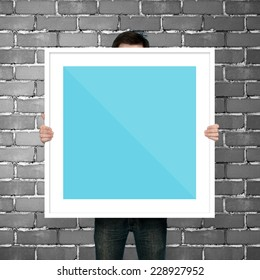 man holding frame on gray background