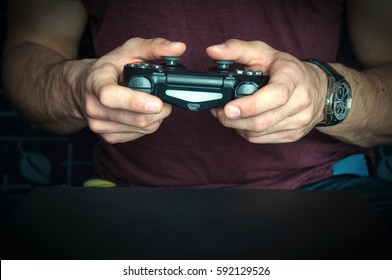 Man holding game controller sitting on ble sofa.