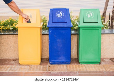 A man holding garbage into recycle bin.Row of different waste bin at the public park.