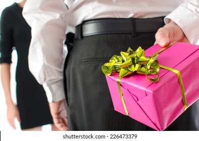 Man holding a gift behind his back in front of a woman