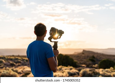 Man holding gimbal camera stabilizer filming sunrise with sunburst flare through equipment in Arches National Park, Utah at Fiery Furnace Viewpoint