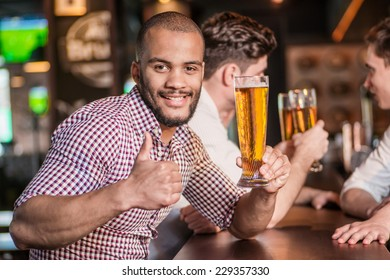 Man holding a glass of beer in hand while sitting at the bar and shows thumb up. Three other men drinking beer and having fun together in the bar until the bartender communicates with them