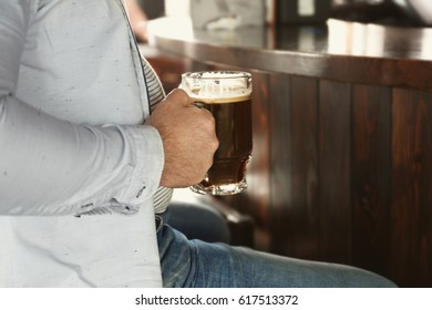 Man holding glass of beer in pub, closeup