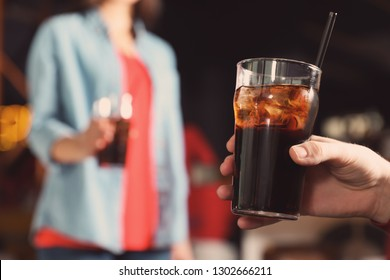 Man holding glass of cola in bar, closeup. Space for text