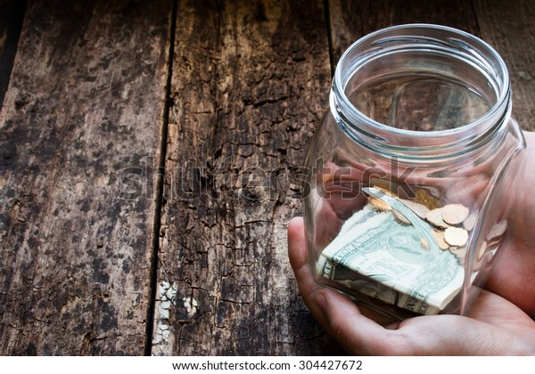 man holding a glass jar for donations