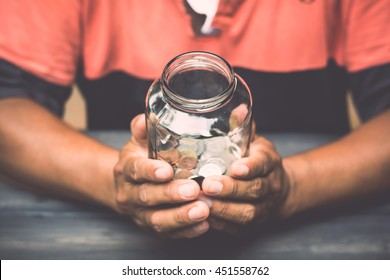 A man holding a glass jar that are money for a savings on wooden table
