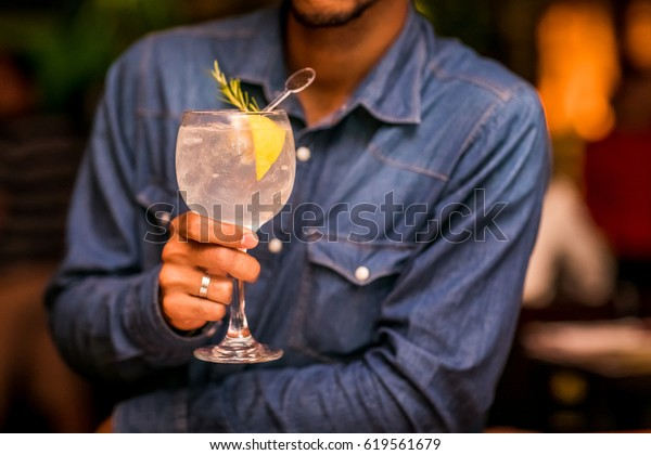 A man holding a glass of tonic gin