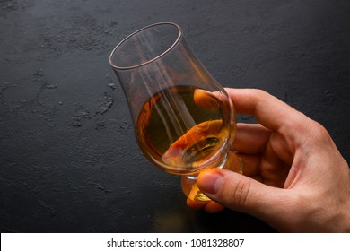 man holding a glass of whiskey on a black background