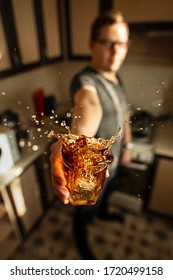 A man holding a glass of whiskey with splashes in the kitchen. Creative lockdown.