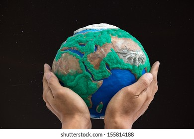 man holding globe made from clay on his hands  with dark sky and star background