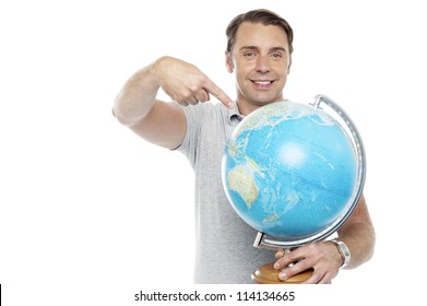Man holding globe and pointing over it against white background