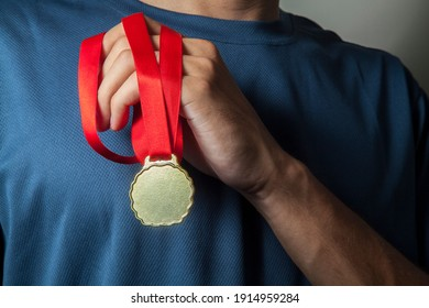 Man holding gold medal with hands at chest height and with a neutral bottom.  Award concept.