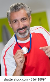man holding a gold medal winner in a competition