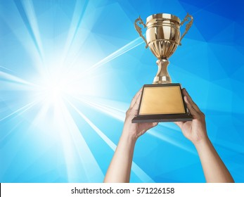 a man holding up a gold trophy cup with abstract blue light and modern background copy space ready for your trophy design.