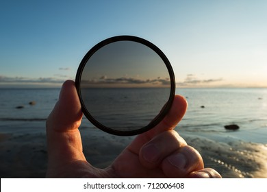 Man holding gradient neutral density ND filter on background of sea and sky