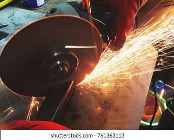 Man holding grinder machine,cutting metal