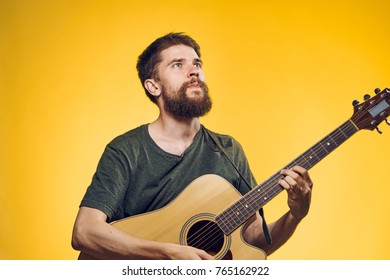 man holding a guitar and looking up on a yellow background.