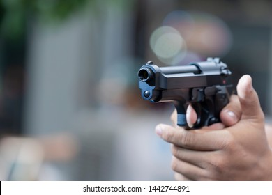 Man holding gun aiming pistol in hand ready to shoot. The criminal robber or gangster thief  concept