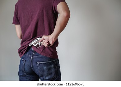 A man holding a gun on his back. The gunman held his gun behind him.Crime Concept.Criminality Concept.Isolated background