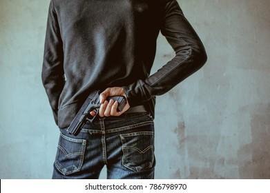A man holding a gun on his back. The gunman held his gun behind him.Crime Concept.Criminality Concept.