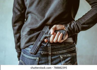 A man holding a gun on his back. The gunman held his gun behind him..Crime Concept.Criminality Concept.