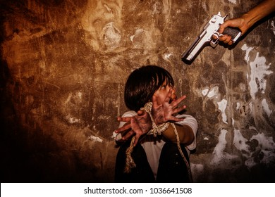 Man holding a gun.Sexual harassment , stop violence against Women, international women's day,Helpless young woman hands tied with rope, Hostage, human trafficking and violence concept