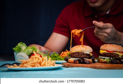 Man holding hamburger on the wooden plate after delivery man delivers foods at home. Concept of binge eating disorder (BED) and Relaxing with Eating junk food.