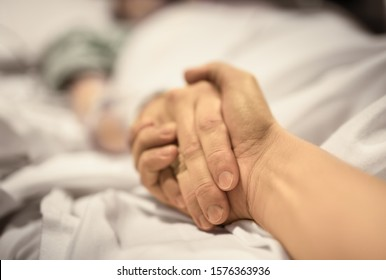 Man holding hand, giving support and comfort to woman, loved one sick in hospital bed.