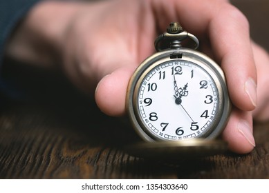 Man is holding in hand a pocket watch on a brown table background.