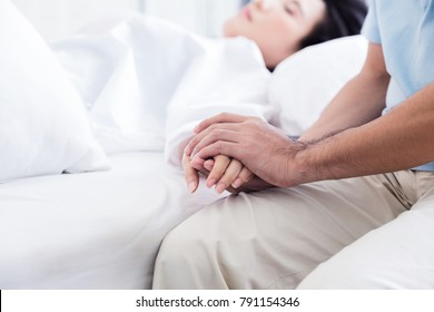 man Holding the hand of a sick loved one in hospital bed health ideas conept