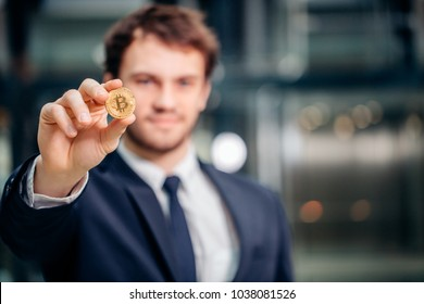 Man holding in hand symbol of bitcoin crypto currency - electronic virtual money for web banking, blurred man on background