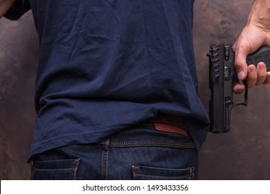 A man holding a handgun in his arm