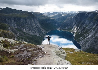 man holding hands up and enjoying view on lake in Norway mountains